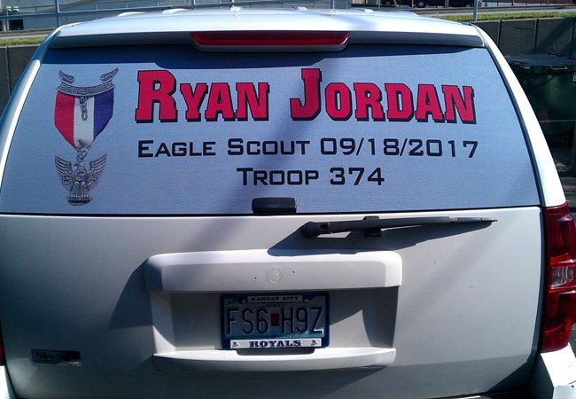 Custom Graphics & Vinyl Decals | Window Graphics | Nonprofit Organizations and Associations Signs | Kansas City, MO | Eagle Scout car decal | Car decals | Car window decal | Window perf